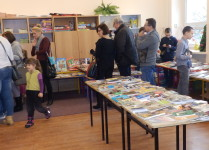Kiermasz książek. Na stołach rozłożone książki o różneje tematyce. Dorośli i dzieci wybierają najciekawsze tytuły