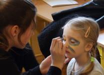 Malowanie twarzy. Mama maluje dziewczynce twarz.