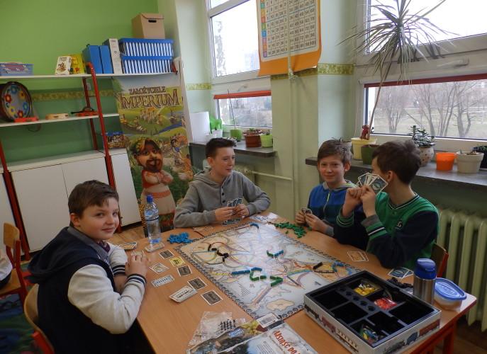 Chłopcy z klasy szóstej siedzą przy stolikach i grają w gry strategiczne
