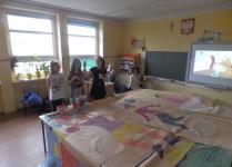 Dziewczynki na ogromnych arkuszach szarego papiru malują jak aktywnie można spędzać wolny czas