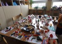 Na stolikach poukładane prace dzieci z masy solnej przedstawiające zdrowe produkty żywieniowe