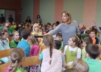 Autorka rozmawia z dziećmi. Na zdjęciu autorka podaje mikrofon dzieciom.