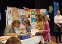 Trzy dziewczynki w kolejce po autograf od autorki