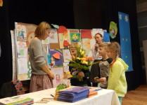 Troje dzieci wręcza kwiaty Pani Elizie Piotrowskiej w podziękowaniu za odwiedziny w naszej szkole