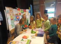 Grupa dzieci w oczekiwaniu na dedykację w książce