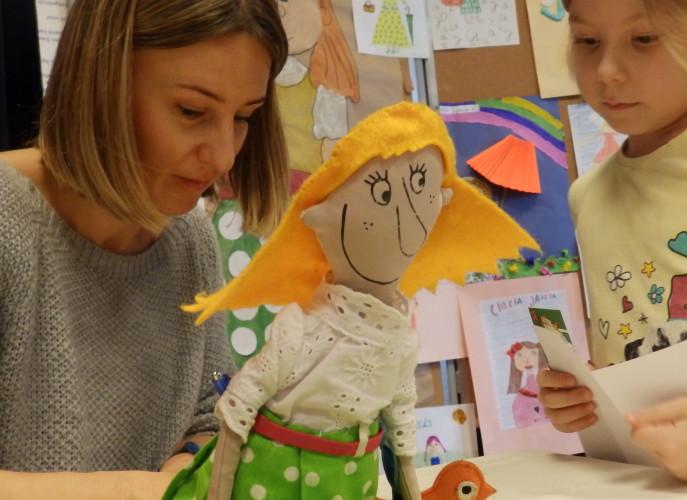 Na pierwszym planie szmaciana lalka cioci Jadzi. W tle pani Eliza Piotrowska podspiująca ksiązkę dziewczynce.