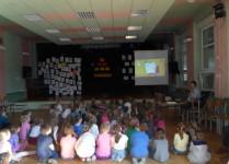 Dzieci w auli szkoły oglądają prezentację multimedialną