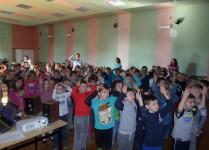 Dzieci w auli szkoły stoją i trzymają się za głowy