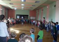 Dzieci stoją w ogromnym kole w auli szkoły