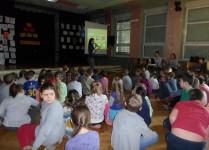 Dzieci siędzą na podłodze w auli szkoły oglądają prezentację multimedialną
