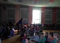 Dzieci w auli szkoły odpwiadają do mikrofonu na pytania zadawane przez organizatorki spotkania