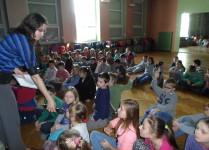 Dzieci siedzące na podłodze w auli zgłaszają się do odpowiedzi