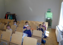 Dzieci, które pojechały na konkurs języka angielskiego, czekają na zadania siedząc na krzesełkach w sali lekcyjnej