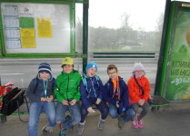 Dzieci siedzą na ławeczce na przystanku tramwajowym w czasie powrotu do szkoły