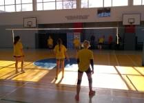 Dziewczynki w żółtych koszulkach w czasie meczu siatkówki