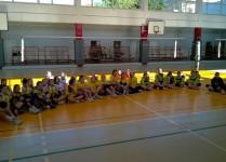 trzy drużyny dziewcząt siedzą na podłodze w sali gimnastycznej w czasie odprawy przedmeczowej