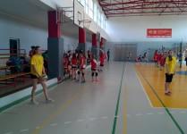 na zagrywce dziewczynka w żółtej koszulce, w tle drużyna dziewcząt w czerwnonych koszulkach