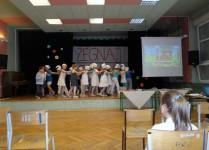 Dzieci w strojach smerfów tańczą na scenie