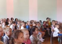 Dzeci z klas pierwszych i oddziałów przedszkolnych wraz z rodzicami i wychowawcami w auli szkoły podczas przedstawienia