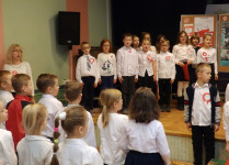 Na scenie dzieci w strojach galowych, stoją na baczność śpiewając hymno państwowy