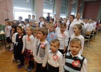 W auli szkolnej dzieci w strojach galowych, z patrritycznymi kotylionami na piersi śpiewają hymn państwowy