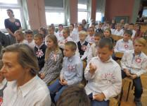 Dzieci w strojach galowych siedzą w auli szkoły
