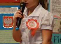 Dziewczynka w białej bluzce podczas recytacji - w tle wystawa o tematyce patriotycznej