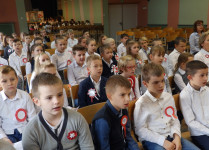 W auli szkoły dzieci oglądają występ kolegów z klas trzecich