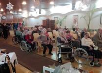 """Seniorzy z Domu Pomocy Społecznej """"Ugory"""" oglądający występy dzieci"""