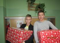 Chłopcy znoszą paczki do holu szkoły