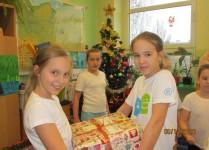 Dziewczynki niosące paczkę z podarunkami
