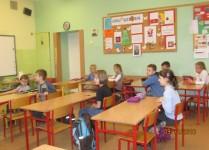 Dzieci siedzące w ławkach, czekają na rozdanie kart konkursowych