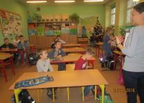 Dzieci słuchające nauczyciela omawiającego zasady konkursu