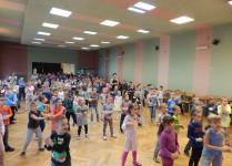 """W auli szkoły, dzieci ustawione w """"rozsypce"""" wspólnie tańczą"""