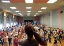 Na scenie tańcząca tyłem nauczycielka, w tke widać dzieci naśladujące jej ruchy