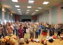 Na scenie leżą misie, za nimi tańczące dzieci z oddziałów przedszkolnych