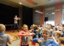 Nauczycielka na scenie pokazuje dzieciom figury taneczne