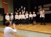 DZieci na scenie ubrane w białe bliuzki i czapki Mikołaja