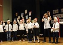 Dzieci z klasy 0b tańczą i śpiewają na scenie