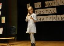 Dziewczynka w szarej sukience śpiewa na scenie