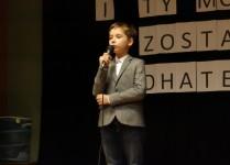 Chłopiec w szarej marynarce śpiewa na scenie