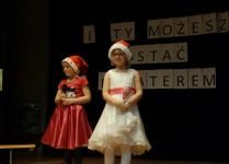 Dwie dziewczynki, jedna w białej druga w czerwonej sukience podczas występu na scenie