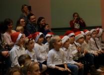 Dzieci z klasy 0b w czapkach Mikołąja w czasie słuchania koncertu