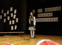 Dziewczynka w czarno-białej sukience spiewa na scenie