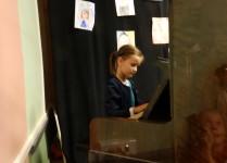 Dziewczynka w zielonej sukience podczas gry na pianinie