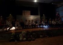 przyciemnione światło, dzieci na scenie, przed sceną usadzone są pluszowe misie
