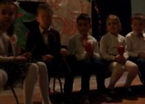 Chłopcy i dziewczynki w strojach galowych grają na instrumentach perkusyjnych
