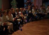 Dzieci siedzące w rzędzie na scenie podczas śpiewania kolęd