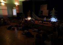 Dzieci leżą na podłodze na scenie i śpią