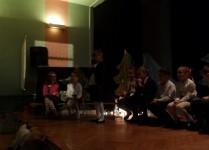 Dzieci w strojach galowych na scenie, jedna z dziewczynek recytuje